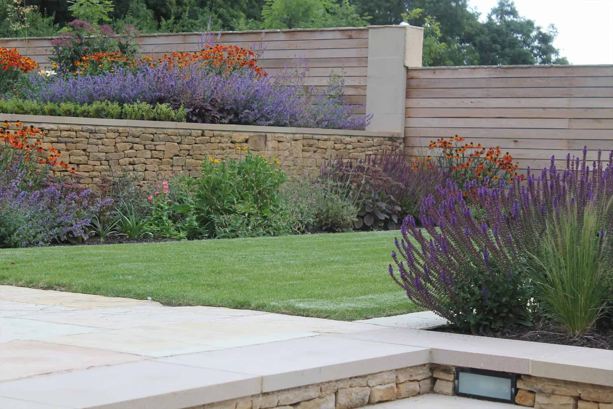 Modern terraced garden with level lawns and colourful planting for Outdoor patio landscaping