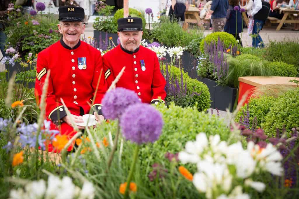 2 Chelsea Pensioners enjoying a cup of tea on the The Sir Simon Milton Foundation Garden, Chelsea flower show garden design by Bestall & Co