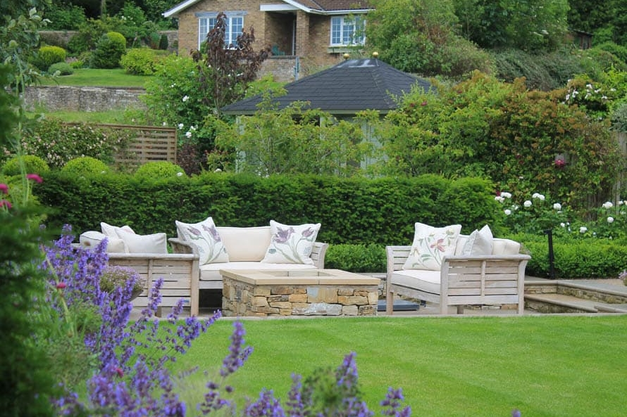 View across a small modern country garden with outdoor sofas, perfect lawn and herbaceous borders this garden look out on beautiful views.